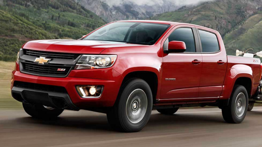 2015 Red Chevy Colorado pulling trailer in mountains