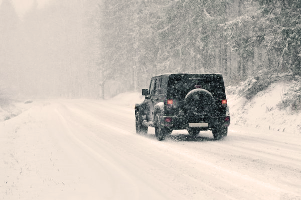 Jeep Wrangler driving through snowy winter conditions
